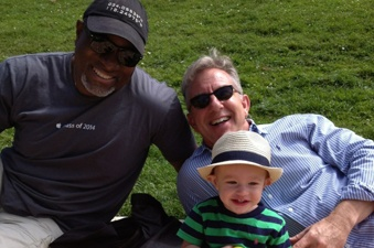 Tom Harshman relaxing with family on a grassy lawn