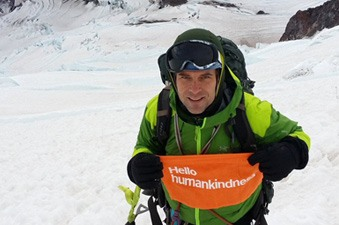 Michael Seagraves poses on a snowy mountain trail  with a Hello Humankindness banner