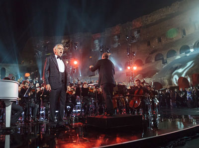 Singer Andrea Bocelli sings from a stage at the Coliseum in Rome