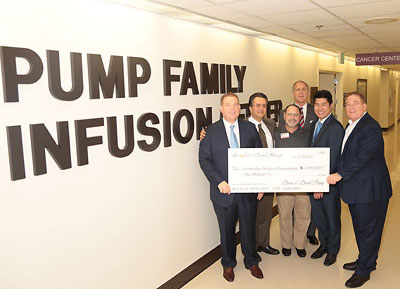 A group holds a check showing the donation amount at the Pump Family Infusion Center