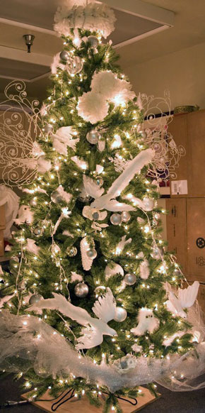 A Christmas tree, decorated with white lights, tulle, and dove ornaments